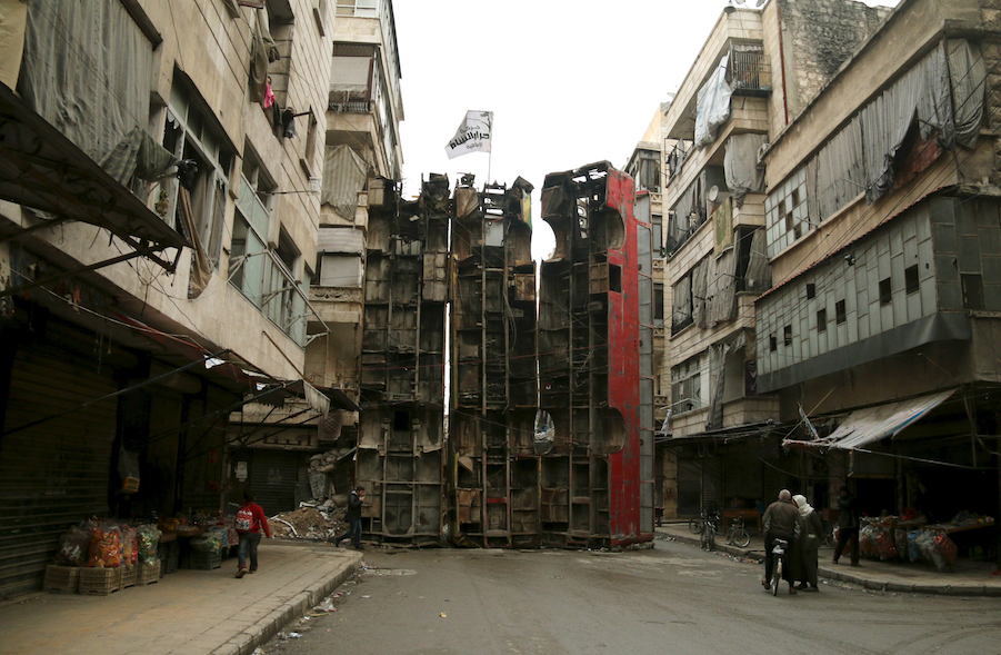 Civilians walk near upright buses barricading a street, which serve as protection from snipers loyal to Syria's President Bashar al-Assad, in Aleppo's rebel-controlled Bustan al-Qasr neighbourhood March 21, 2015. Picture taken March 21, 2015.  REUTERS/Ammar Abdullah      TPX IMAGES OF THE DAY      - RTR4UEN4